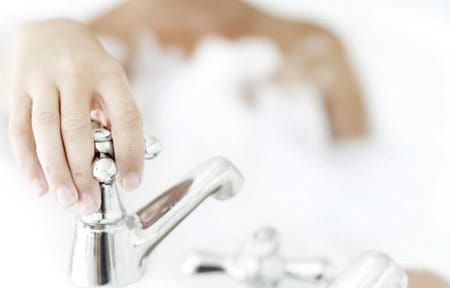Hand on faucet