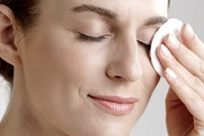 Woman removes eye make-up with a cotton pad.