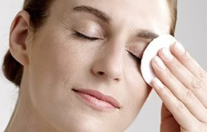 Woman removes eye make-up with a cotton pad