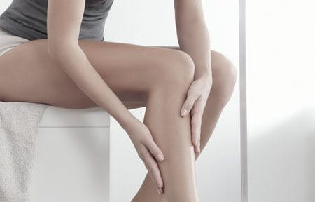 Woman applying care product to her leg.