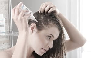 Woman applying product to scalp