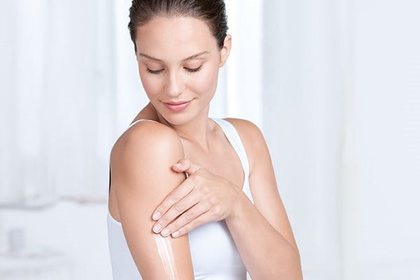 Woman applies body lotion for sensitive skin