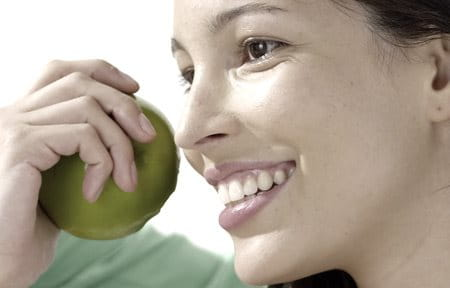 Woman smiling and holding a green apple in her hand