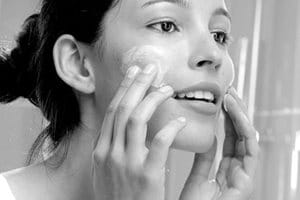 Woman appliying cream on her face