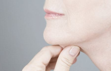 Woman pulling her chin skin with hand.