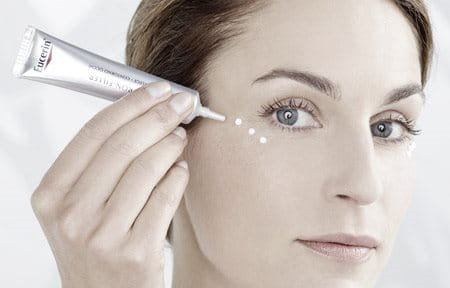 Woman applying drops of cream on her right cheekbone.