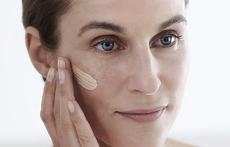 Woman applying Eucerin Hyaluron-Filler CC Cream on her right cheekbone.