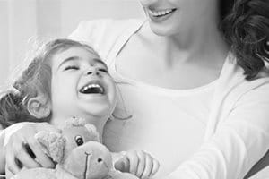 Little girl lying in mother´s arm, laughing and holding a stuffed animal.