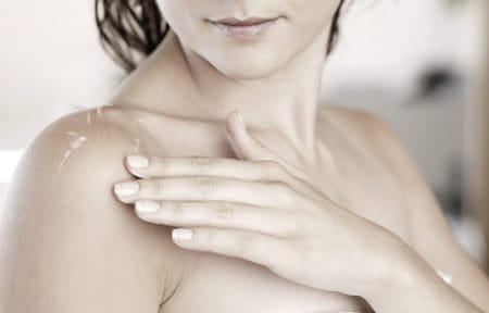 Woman with wet skin touching her shoulder