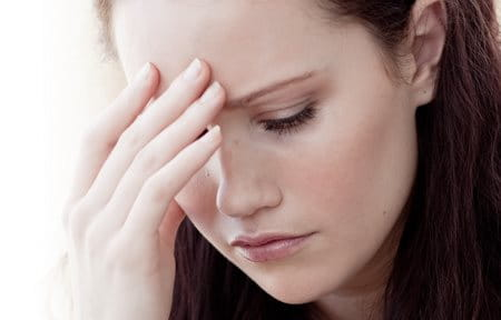 Stressed woman with hand to forehead.