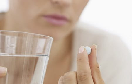 Woman with glass of water about to swallow a tablet