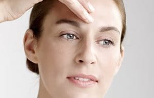 Woman applies concentrate on her forehead