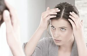 Woman looking at her scalp in the mirror